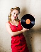 stock photo of rockabilly  - Portrait Of A Happy Rockabilly Music Girl Holding Retro Vinyl Record Lp On Grunge Background - JPG