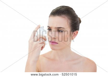 Puzzled natural brown haired model looking at an asthma inhaler on white background