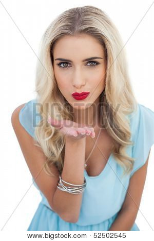 Seductive blonde model in blue dress sending a kiss to the camera on white background