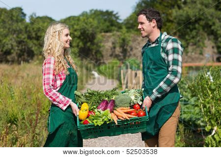 Young couple carrying vegetables in their garden smiling at each other