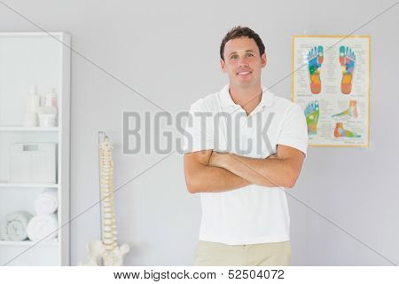 Handsome smiling physiotherapist standing with arms crossed in bright office