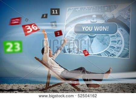 Businessman sitting on deck chair looking at holographic screen and numbers on the beach
