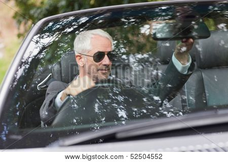 Mature businessman adjusting his cabriolet rear view mirror while driving