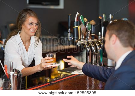 Beautiful waitress serving handsome businessman in a classy bar