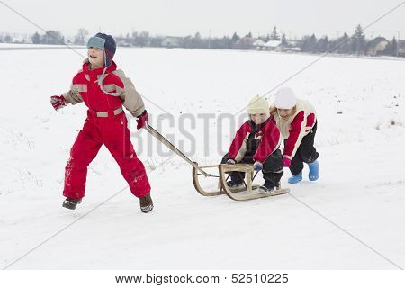 Children makes winter fun with sledge outdoor