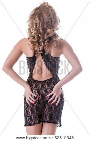 Curly girl posing in lacy negligee back to camera