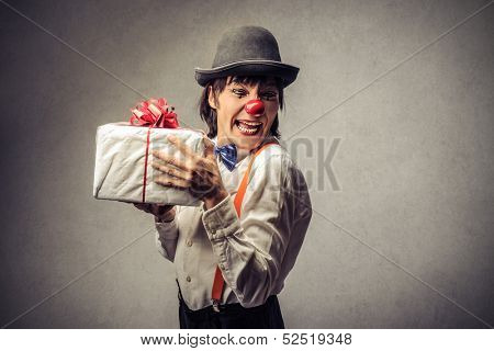 clown with red nose and bowler hat shows a gift
