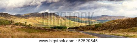 Dramatic sky over the glen with road running through. Scottish Highlands, UK