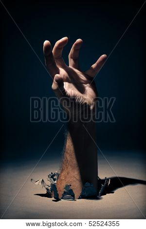 Hand coming through a hole clawing or reaching out for help - concept for mental illness or assistance