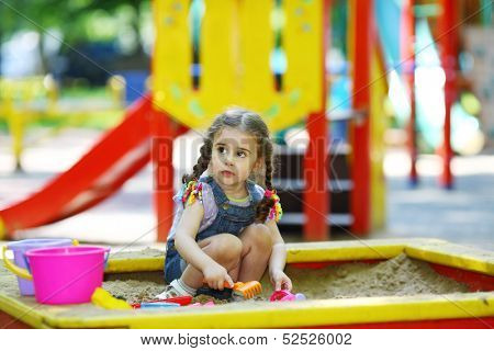 Little girl playing with molds in the sandbox on the playground