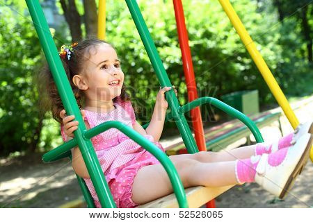 Laughing little girl in a pink dress swinging on a swing at the playground
