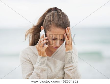 Frustrated Young Woman In Sweater On Beach Talking Cell Phone