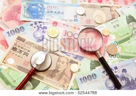 Asian Currency, Magnifying Glass And Stethoscope With Background Of Asian Currency