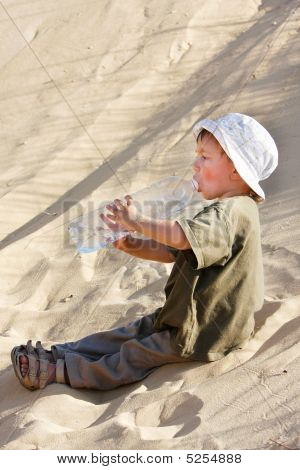Young Boy Drinking Water In Sand Desert