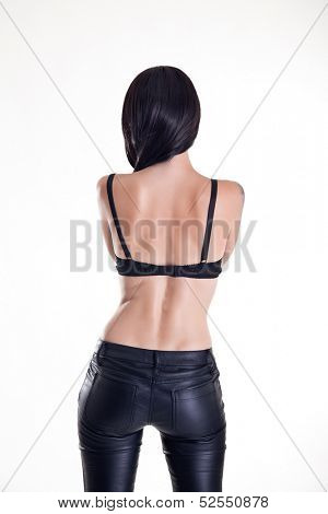 Rear view of beautiful woman wearing leather pants and bra, studio shot