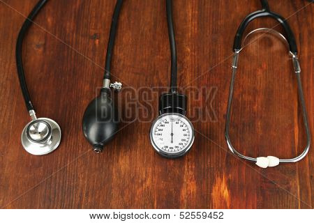 Tonometer and stethoscope on wooden table close-up