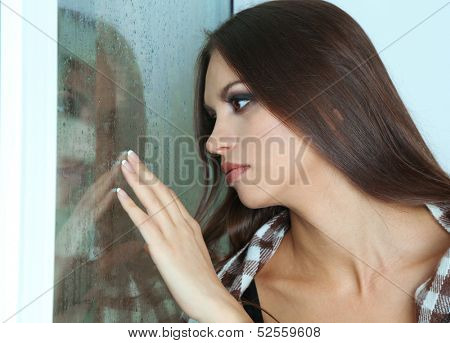 Lonely sad woman looking through window