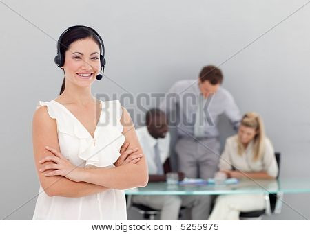 Businesswoman Talking On A Headset With Folded Arms