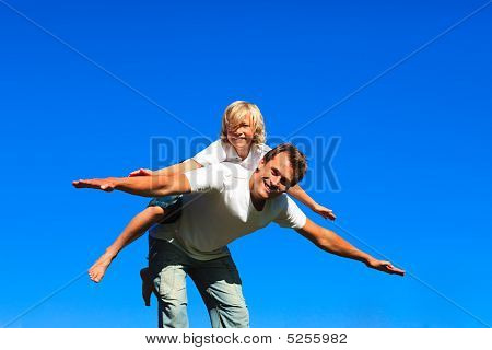 Child On Father's Back Playing Airplane