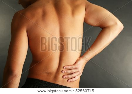 Young man with back pain on grey background