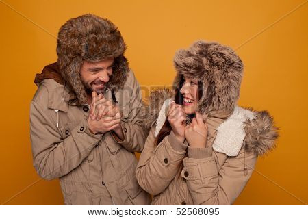 Happy couple in warm winter clothing wearing warm furry caps and jackets laughing as they stand looking at each other rubbing their hands against the cold, on an orange studio background
