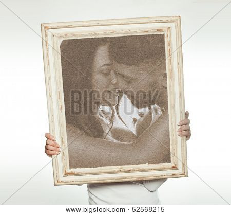 Woman holding a romantic sepia toned picture of a couple in love with their foreheads touching so that it conceals her face and upper body, isolated on white