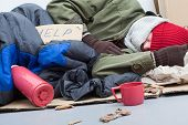 stock photo of sleeping bag  - Homeless man sleeping on cardboard with sleeping bag and thermos - JPG