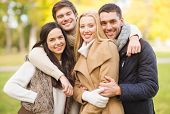 summer, holidays, vacation, happy people concept - group of friends or couples having fun in autumn