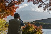 MOUNT FUJI - NOVEMBER 7: A man photographs Mount Fuji through fall foliage November 7, 2012 in Mount