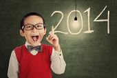 stock photo of shot glasses  - Asian genius student with light bulb and number of new year 2014 shot in a classroom - JPG