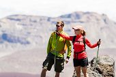 picture of mans-best-friend  - Man and woman hikers trekking in summer mountains. Young couple on rocky mountain range looking at beautiful view.