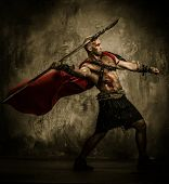 stock photo of legion  - Wounded gladiator in red coat throwing spear - JPG