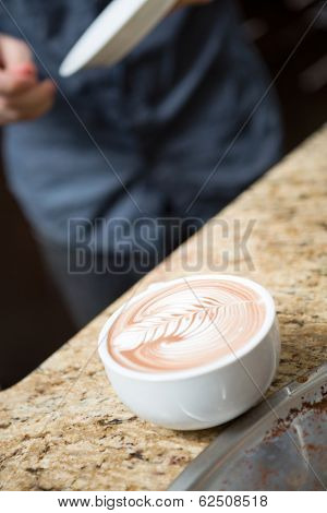 Closeup of cappuccino at counter in coffeeshop