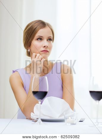 reastaurant and happiness concept - upset young woman with glass of red whine waiting for date at restaurant