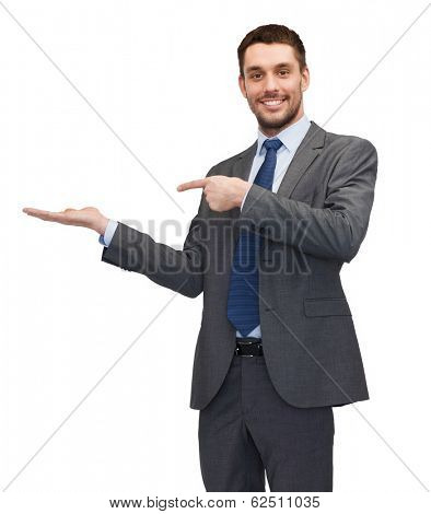 business, office, advertising and people concept - friendly young buisnessman pointing finger to something on the palm of his hand