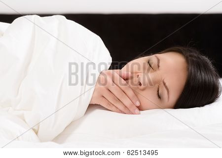 Young Woman Lying In Bed Yawning