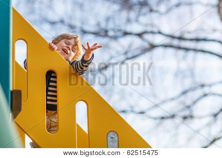 Adorable Toddler Boy Having Fun And Sliding On Outdoor Playground