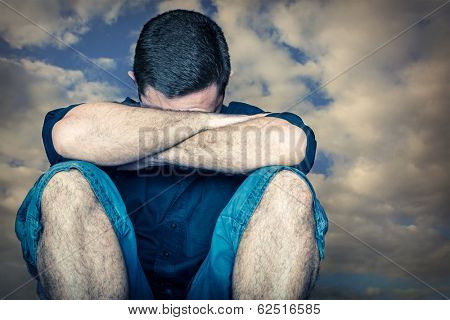 Sad young man hiding his face and crying with a stormy clouds background