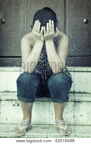 Grunge portrait of a depressed woman sitting on a stairway and crying