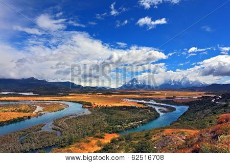Meandering river bed of yellow autumn coast. Valley surrounded by snow-capped mountains. Glen Serrano