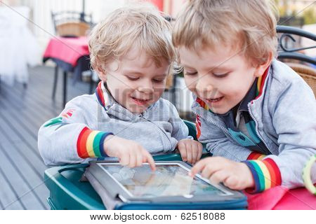 Two Little Sibling Boys Having Fun Together With Tablet Pc.