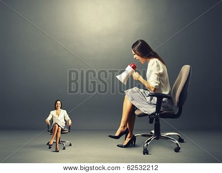 angry young woman screaming at smiley calm woman on the chair over dark background