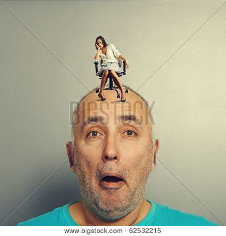 amazed man with small tired woman on his head over grey background