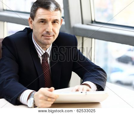 Business man smiling while working on tablet pc in his office