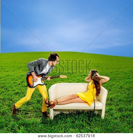 Man Playing A Solo On The Guitar With Girl Lying On The Couch And Singing Together On The Green Fiel