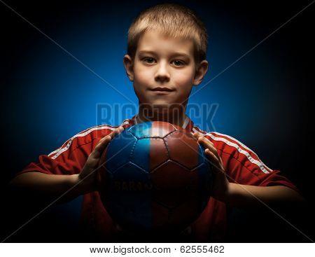 Cute boy is holding a football ball