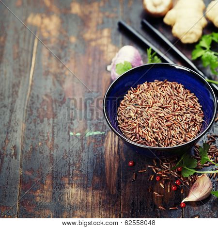 wild rice in ceramic bowl and asian ingredients on wooden background
