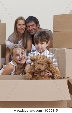 Children Unpacking Boxes With Their Parents