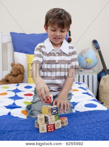 Little Boy Playing With Alphabet Cubes In His Bedroom