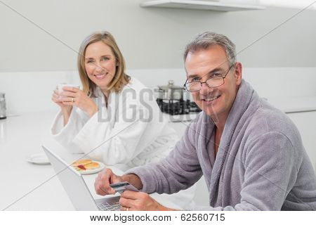 Happy couple in bathrobe doing online shopping through laptop and credit card at home